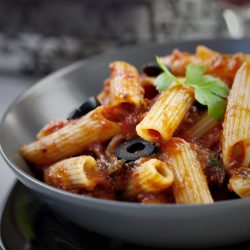 Italian food. Pasta penne with tomato sauce, olives and garnish