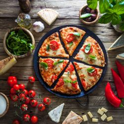 Pizza on wood with ingredients. Pizza with cheese, tomatoes and basil. Rustic italian pizza