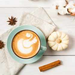 Pumpkin spice latte. Blue coffee cup with creamy foam, cinnamon sticks, cloves and small yellow pumpkins at white wood background. Autumn fall hot drinks, cafe and bar concept, top view