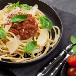 Spaghetti bolognese pasta with tomato and minced meat sauce, parmesan cheese and fresh basil